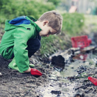Little boy in green raincoat digging intently in mud puddle