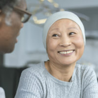 A Korean woman with cancer is meeting with her doctor. Chemotherapy treatment is going well. The patient is smiling at her doctor as he shares with her positive news. (A Korean woman with cancer is meeting with her doctor. Chemotherapy treatment is go