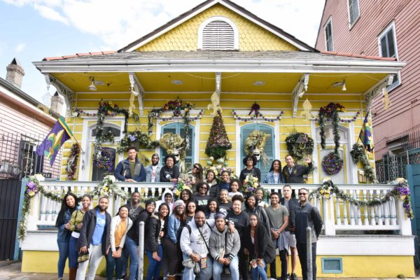 Students on the Black History Immersion Excursion standing in front of a home in the French Quarter decorated for Mardi Gras (Rosevelt Noble/Vanderbilt)