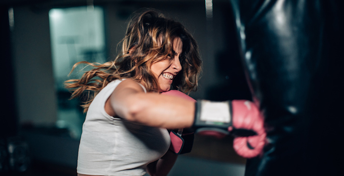 Athletic fair skinned woman with brown hair striking a heavy bag with boxing gloves on