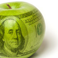 Green apple with a $100 bill superimposed over it to symbolize the cost of education