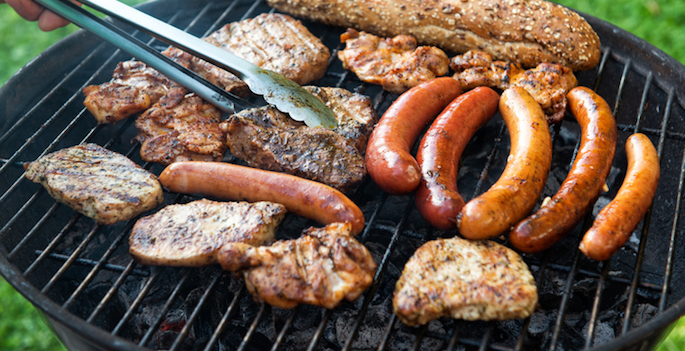 Assorted meat and sausage on grill with the coals, cooking outdoors, weekend concept