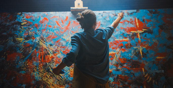 Woman Artist Works on Abstract Oil Painting, Using Paint Brush She Creates Modern Masterpiece. Dark and Messy Creative Studio where Large Canvas Stands on Easel Illuminated. (Talented Female Artist Works on Abstract Oil Painting
