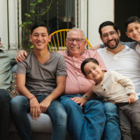 A Latino grandfather sitting on an outdoor sofa surrounded by his sons and grandsons