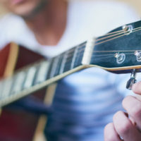 Close-up of young caucasian man tuning a guitar