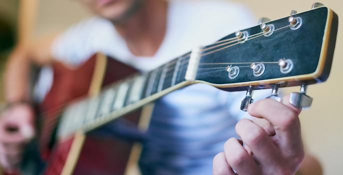 Close-up of young caucasian man tuning a guitar