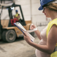 White heavily pregnant woman wearing a blue hard hat and yellow vest looks at a clipboard in a warehouse while a colleague drives a forklift behind her.
