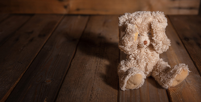 Child abuse concept. Teddy bear covering eyes, dark empty background, copy space
