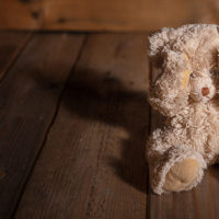 Child abuse concept. Teddy bear covering eyes, dark empty background