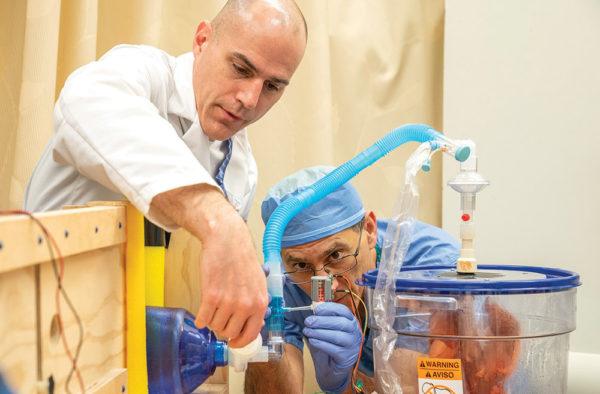photo of two scientists examining ventilator equipment