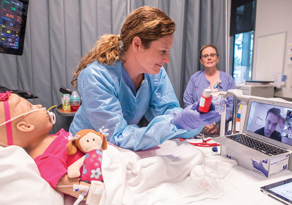 photo of an instructor collaborating with a student remotely on how to provide care to a nursing mannequin