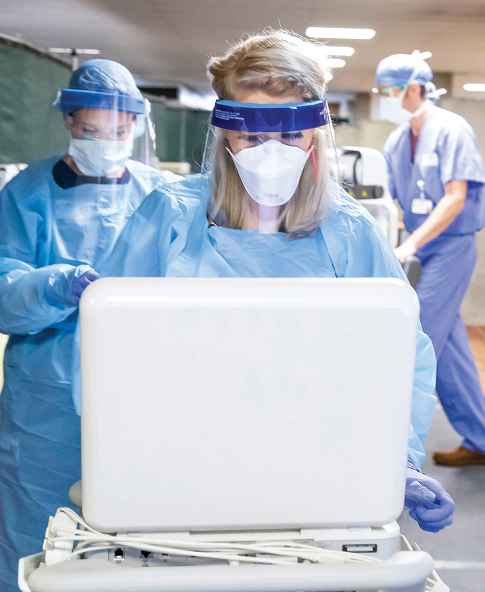 photo of health care workers in masks and scrubs looking at a laptop screen