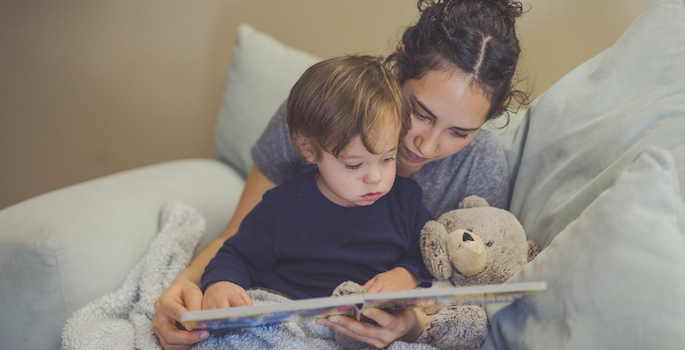 Young Hispanic mom reads a book aloud to her toddler son. They're pointing at the pictures together. A teddy bear is snuggled up with them.