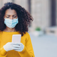 African american woman wearing a face mask walking outdoors and using cell phone