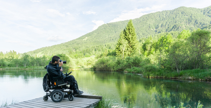 disabled caucasian man using a power wheelchair sitting on a wooden dock taking a photograph of a lake and green trees and hills beyond