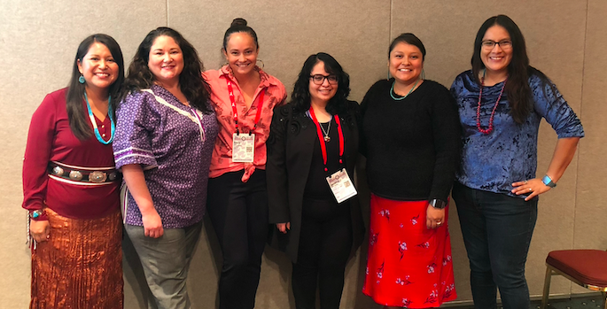 six professional indigenous women, some in cultural dress, smiling in a conference room
