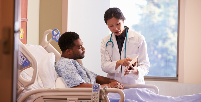 Asian American female doctor discusses care with hospitalized young African American male patient by showing him information on a digital tablet