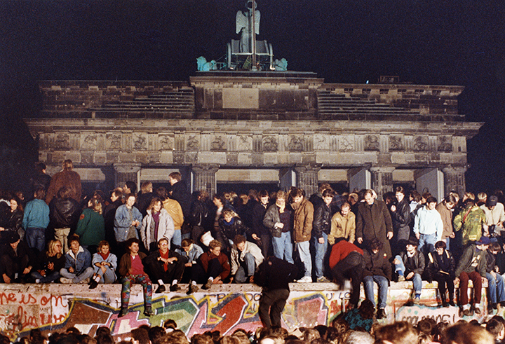 photo of German citizens atop the Berlin Wall in 1989