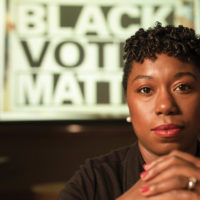 "photo of Charlane Oliver in front of a sign that says ""Black Votes Matter"""