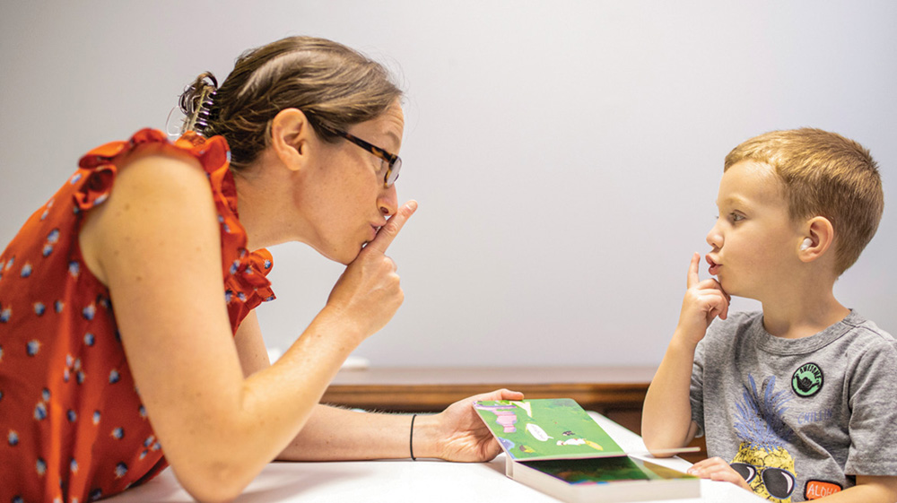 photo of Miriam Lense reading to a young boy