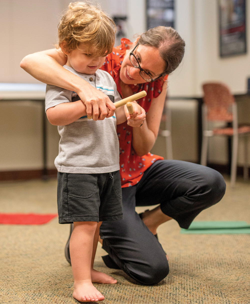 photo of Miriam Lense teaching rhythm to a young boy