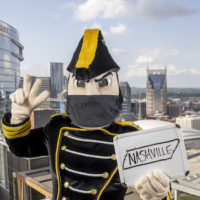 Mr. C in a mask with Nashville skyline in background