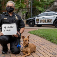 Vanderbilt Police Sergeant Cheryl Bradley with K9 Levi shows who she masks up for as she practices healthy behaviors outside Kirkland Hall.