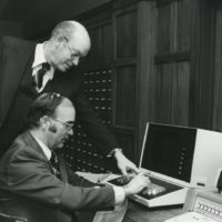 Frank Grisham (standing) demonstrates computer equipment at the Joint University Library. (Vanderbilt University Special Collections and Photo Archives)