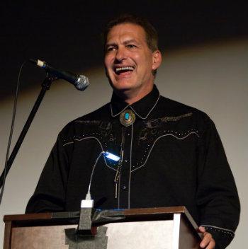 John Bloom, aka Joe Bob Briggs, at podium
