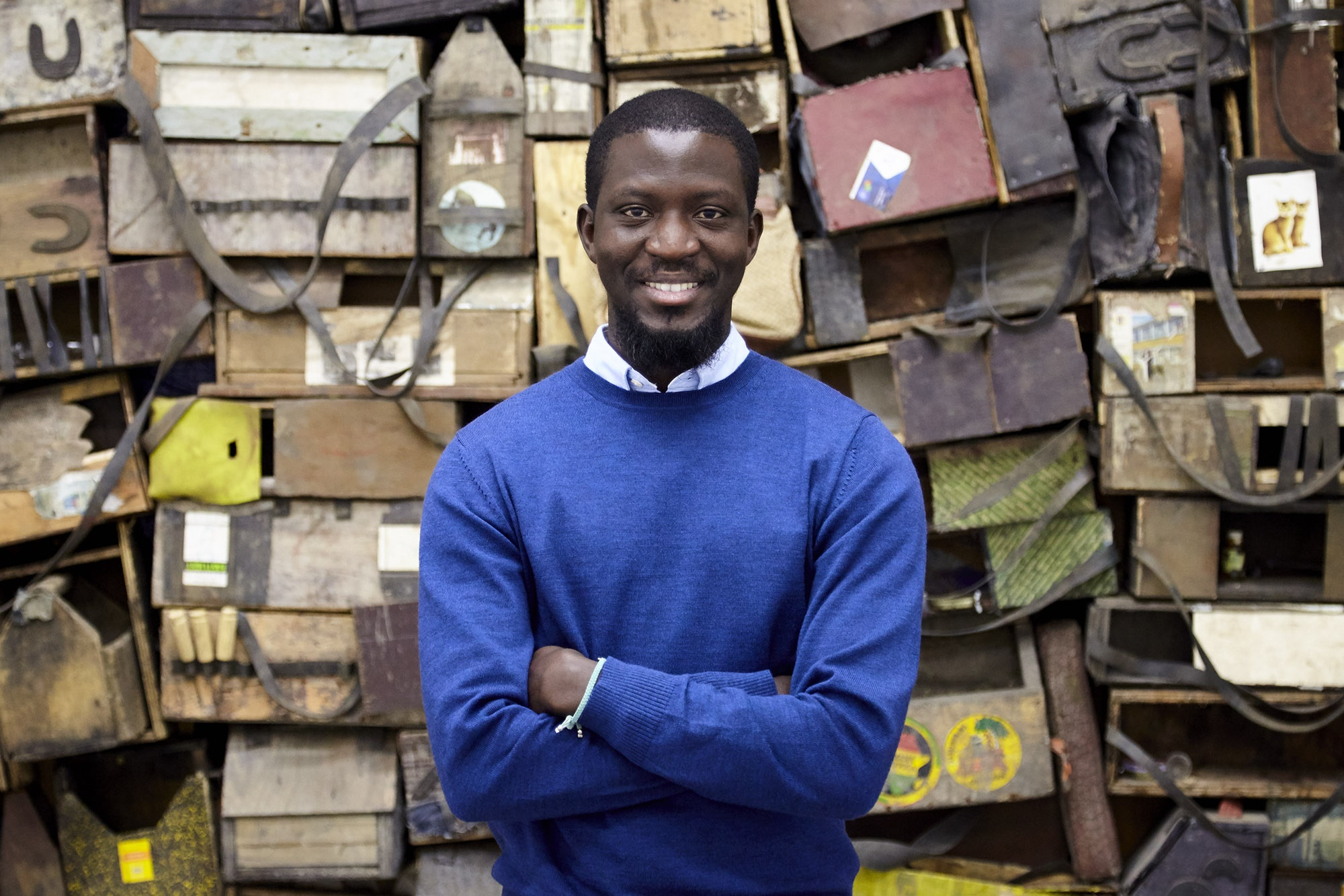 photograph of artist Ibrahim Mahama in front of jute sacks collected at Ghanian markets