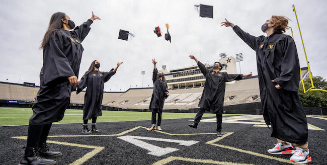 Commencement graduates throwing their mortar boards