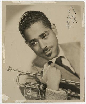 publicity headshot from the 1950s of prominent jazz musician Dizzy Gillespie holding trumpet
