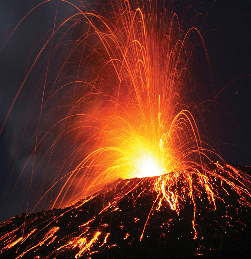 photo of a volcano erupting at night