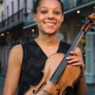 Portrait of Dana Kelley with her viola on an urban street