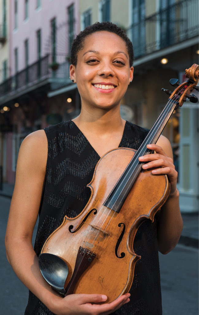 Portrait of Dana Kelley, with her viola, on a street on a city street