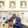 Artist James Threalkill sitting beneath his paintings at the Black Cultural Center