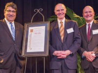 Chancellor Nicholas S. Zeppos (left) and Vanderbilt University Board of Trust Chairman Bruce Evans (right) present Hart with the 2018 Distinguished Alumnus Award. (Vanderbilt University/Anne Rayner)