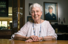 Emily Manchester Townes, BA'50, has preserved her brother's war letters by compiling them into a family history. A portrait of John Manchester hangs behind her. (DANIEL DUBOIS)