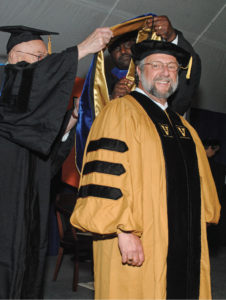 Caruso is hooded by Centennial Professor of Philosophy John Lachs, left, as he receives his Ph.D. in philosophy in May 2016.