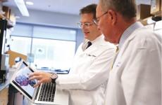Dr. James Crowe, left, gives U.S. Sen. Lamar Alexander, BA'62, a tour of his research lab. (ANNE RAYNER)
