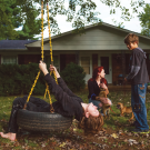 Photo of family playing in front of house