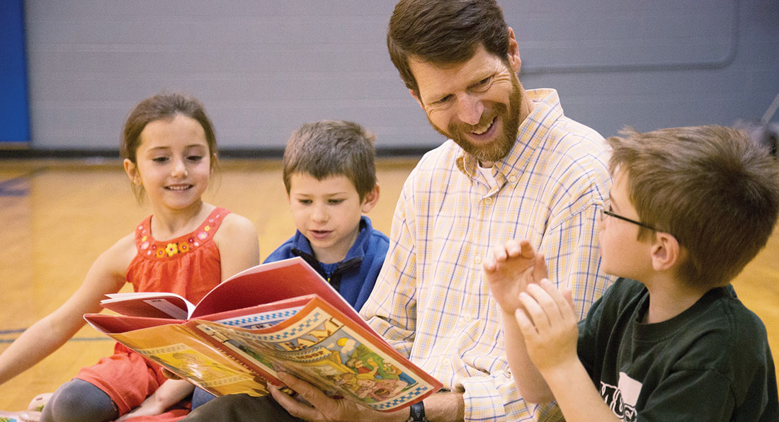 Photo of Duncan McDougall reading to children
