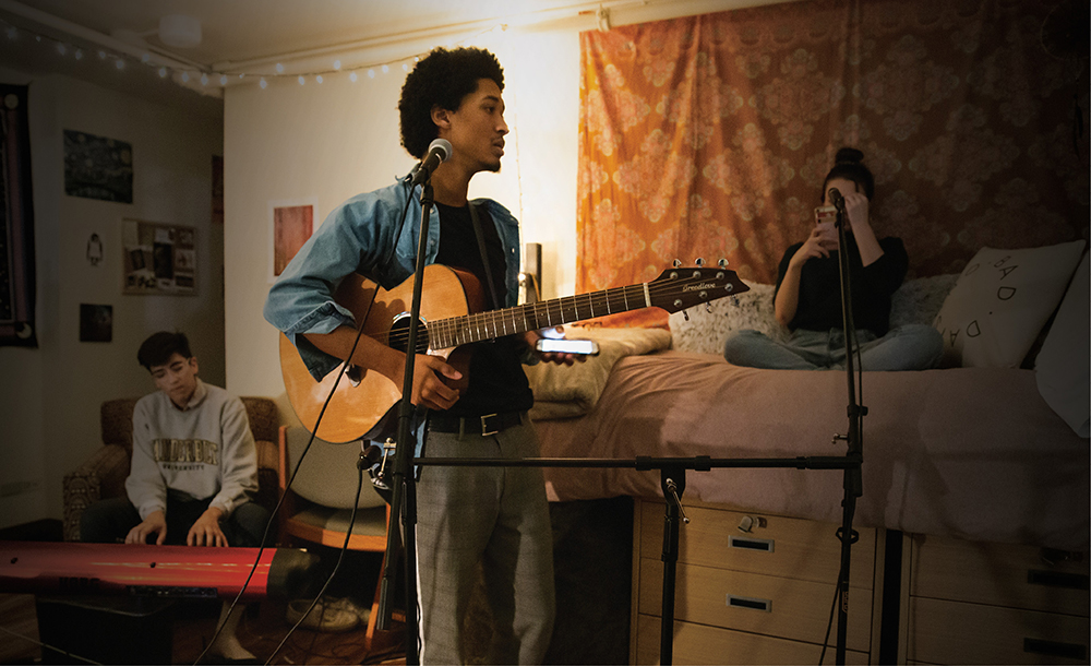 photo of student holding a guitar in a dorm room