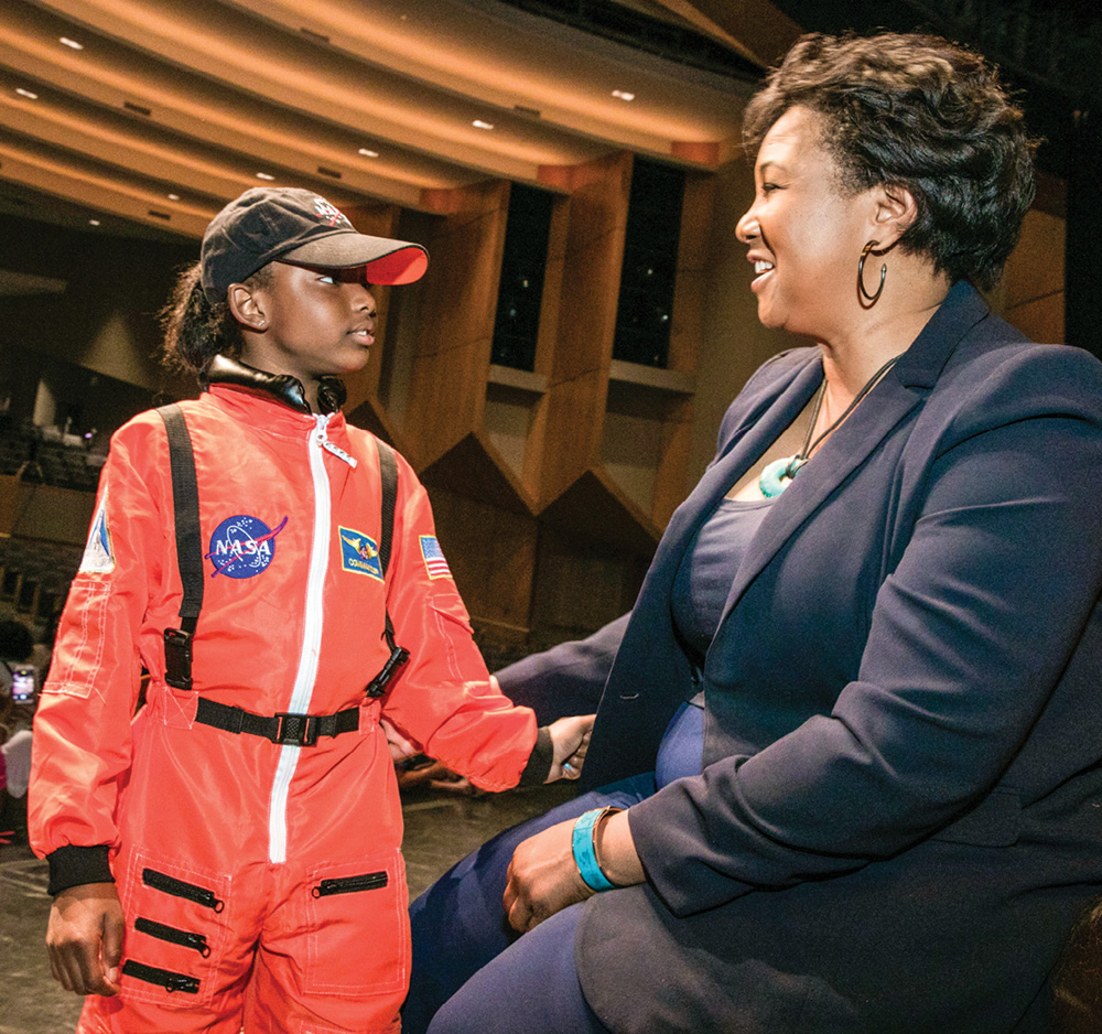 photo of Mae Jemison with a young girl dressed in an astronaut jumpsuit
