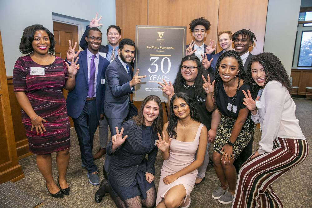 photo of students making the VU gesture with their hands in front of a Posse 30 year sign