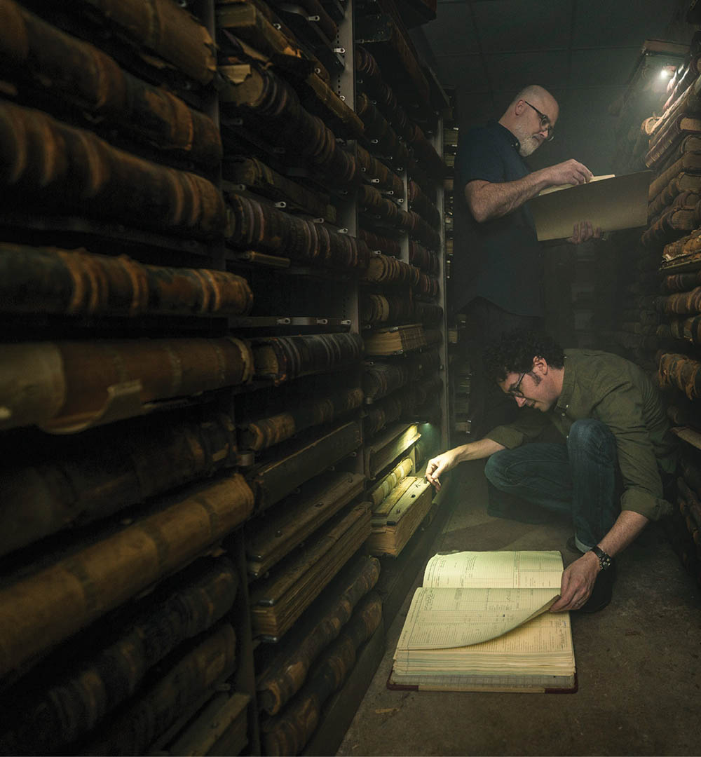 photo of Chip Brantley and Andrew Beck Grace reading old documents by flashlight in a dark room
