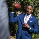 photo of a student in a suit throwing a football