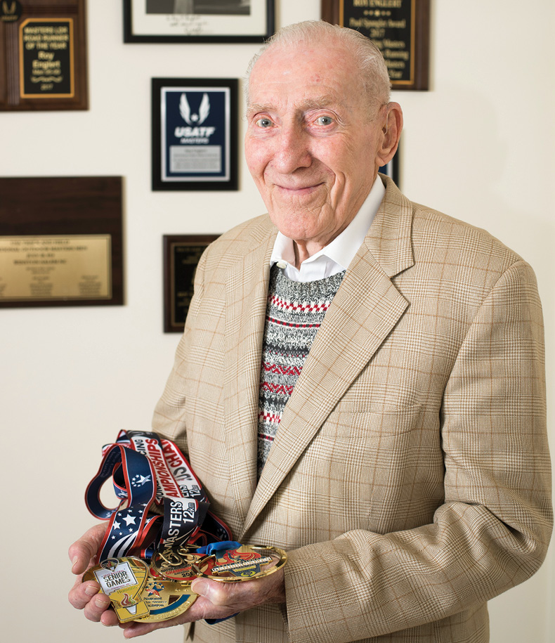 photo of Roy Englert holding several of his running medals