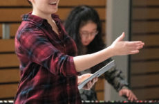 Senior Sarah Clements sings—accompanied by sophomore Calendula Cheng at the keyboards— during the dress rehearsal for January's concert A Humming Under My Feet. Photo by Joe Howell