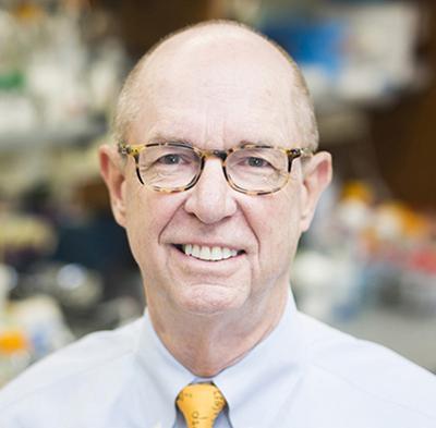 Headshot of Larry Marnett wearing tortoise-shell eyeglasses, a blue shirt, and a yellow tie.